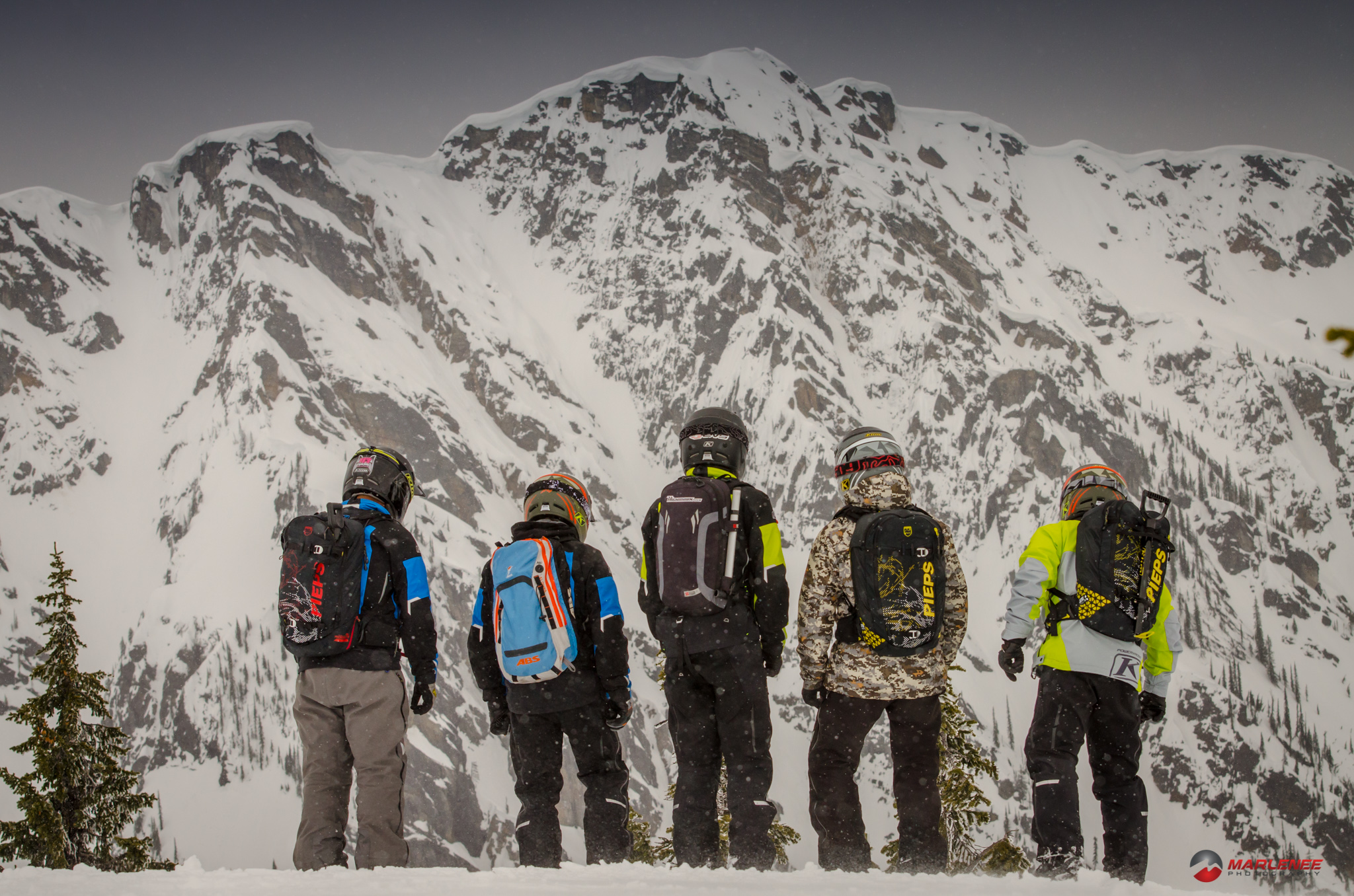 Cole Willford, Jared Sessions, Matt Entz, Dan Adams, Trennis Baer, and Sid Huntsman peer over a cliff in Revelstoke, BC